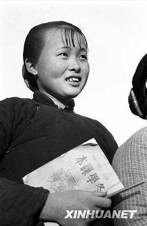 """(图为1950年12月浙江杭县挟着课本去""""冬学""""的农村妇女 新华社记者王纯德摄)"""