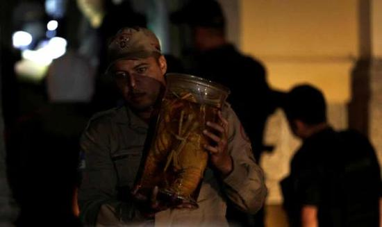一名消防队员在博物馆火灾中救出物品的照片