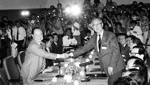 """1993年4月27日""""汪辜会谈""""前汪道涵(左)与辜振甫握手的资料照片。"""