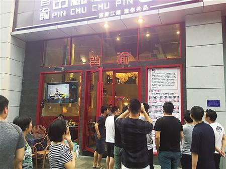 餐馆门口张贴的千字海报引路人围观