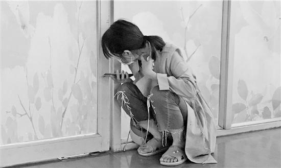 张婷从ICU病房门缝里往里面看,心牵烫伤的儿子。