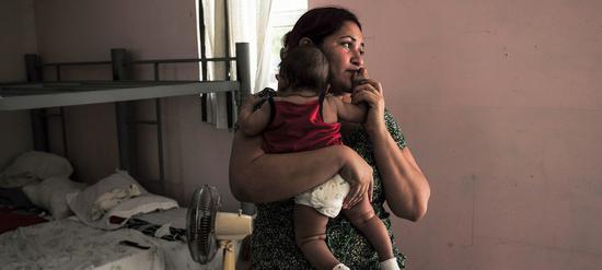 一位移民母亲与孩子在庇护所中。(图:美联社)