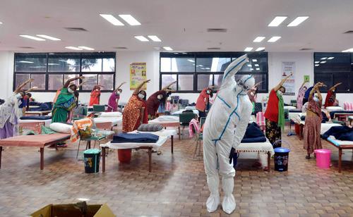 7月24日,医务人员和患者在印度首都新德里的一所新冠治疗中心做瑜伽。新华社发(帕塔·萨卡尔摄)