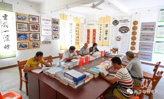 丹村村干部和村民在村文化室内读书(5月9日摄)。
