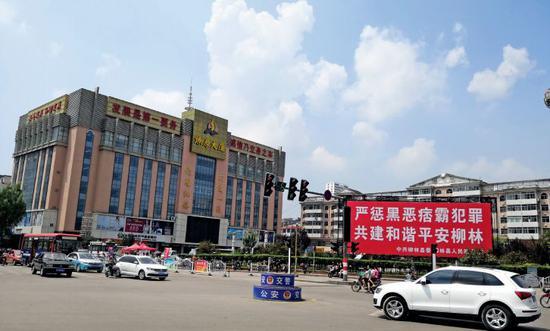 在山西省柳林县,陈鸿志控制的燎原大厦 是当地的高档商厦,其广场前的扫黑除恶的 宣传标语格外醒目。摄影/周群峰