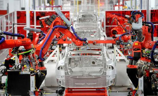 这是2012年6月22日,在美国加利福尼亚州弗里蒙特的特斯拉工厂,机器人手臂组装汽车零件。