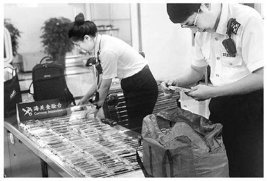 图为海关工作人员在检查旅客携带的假睫毛。王咏洁 摄