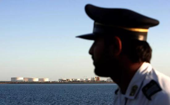 ▲资料图片:伊朗恰巴哈尔,一名保安望向远处的石油港口。(路透社)