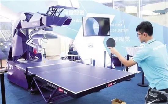 一名工作人员在2018世界人工智能大会现场演示与机器人打乒乓球。 (新华社发)