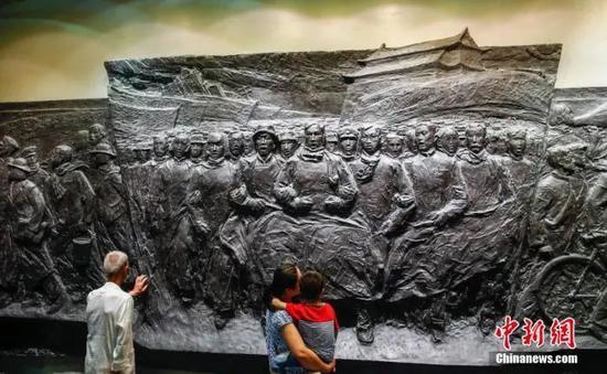 资料图:民众参观北京宛平城内中国人民抗日战争纪念馆的浮雕。中新社发 张浩 摄