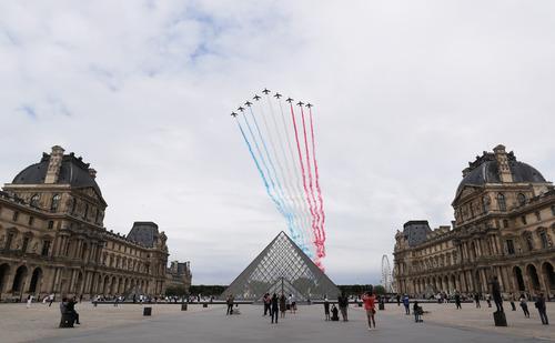 """7月14日,""""法兰西巡逻兵""""飞行表演队飞过法国巴黎卢浮宫玻璃金字塔广场。新华社记者高静摄"""