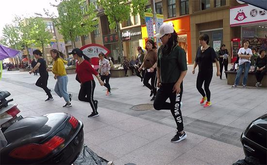 梅丽在出租房楼下的步行街,和小姐妹一起练习跳舞。