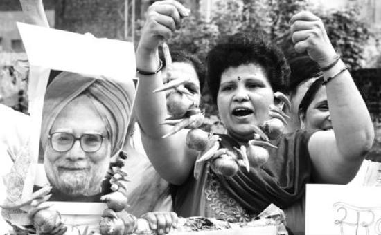 2013年8月22日,印度旁遮普邦阿姆利则市,民众手持时任总理辛格的照片和洋葱,抗议洋葱价格飞涨。图源:中国青年报