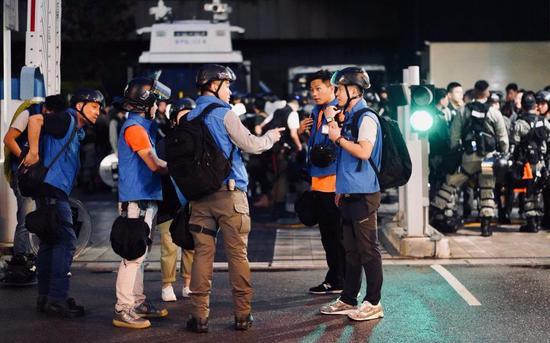 身脱蓝色背心的喷鼻港警圆传媒联系队成员。