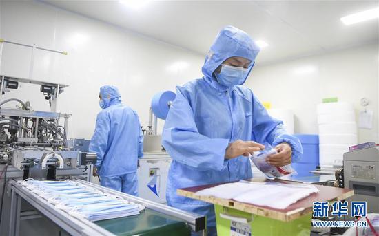 2月11日,工作人员在位于重庆市南岸区的宏冠医疗设备有限公司口罩车间内作业。新华社记者王全超摄