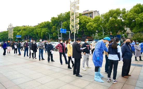 4月14日上午,江夏区纸坊街道郭岭社区住民在市民休闲广场排起长队,守候担当检测。受访者供图
