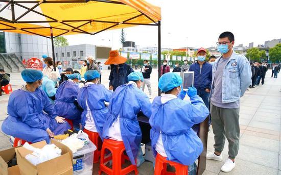 4月14日上午,江夏区纸坊街道郭岭社区抽样观察现场,事情职员为住民摄影,一人建一档。受访者供图