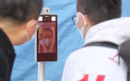 学生测量体温后进入校园。新京报记者 王贵彬 摄