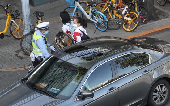 交警帮忙打开车门,提醒家长送孩子即停即走。新京报记者 王贵彬 摄