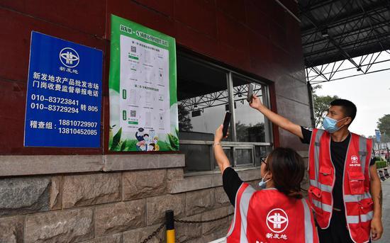 卖家正在扫码,预约进场。摄影/新京报记者 吴宁