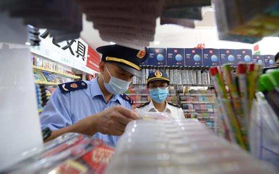 执法人员对一家文具门店内的笔、本等商品进行检查。通州区市场监管局供图