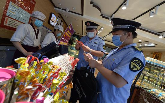 执法人员对校园周边的食杂店、小超市开展检查。通州区市场监管局供图