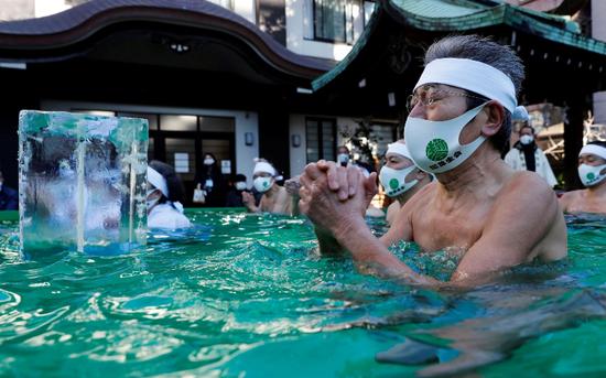 日本民众戴口罩泡冰水浴 祈祷新冠疫情结束(图)