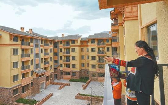 5月13日,某色拉博和孩子们在县城会合安顿点新居阳台上。 记者 尹钢 王云 摄