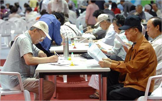 """韩国政府为60岁以上老人举行了""""银发招聘会""""。老人戴着老花镜填写申请表。Seokyong Lee/摄"""