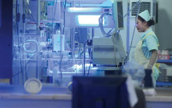 """2011年6月,辽宁省沈阳市妇婴医院,重症监护室的医护人员照看着一名新生婴儿。该名新生儿患有溶血症,急需""""熊猫血"""",家属通过微博在网上求助找到36名献血者,换血后男婴转危为安。图/视觉中国"""