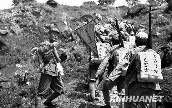 (图为1952年8月部队在行军中后面的战士通过前面一人后背的注音字母学识字 新华社记者岳国芳摄)