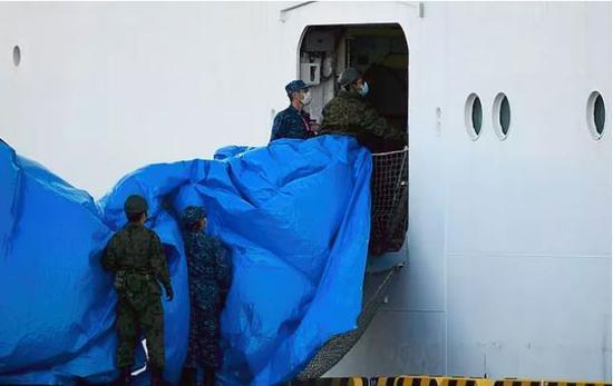 確診人員在層層隔離保護中下船。