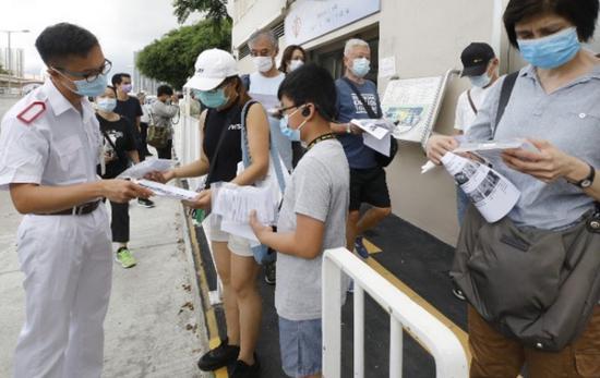 香港市民向门诊职员询问样本瓶使用及交还方法。图源:香港东网