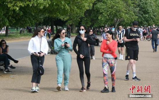 资料图:在伦敦,部分市民佩戴口罩出行,享受休闲时光。 中新社记者 张平 摄