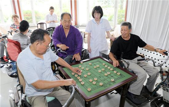 河北省唐山市截瘫疗养院的住院者在下棋(2019年7月25日摄)。新华社记者 赵鸿宇 摄