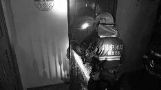 消防人员破拆房门,营救被困人员