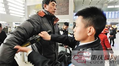 负责安检的聂渝鑫在手检进站乘客。 本报记者 胡杰 摄