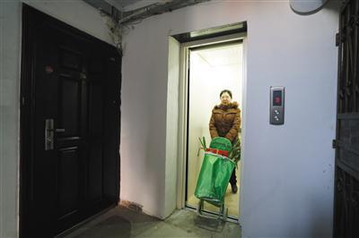 昨日,黄村西里56号楼,大兴区首个老旧楼房加装电梯工程完工。一位居民在使用刚加装好的电梯。新京报记者 吴江 摄