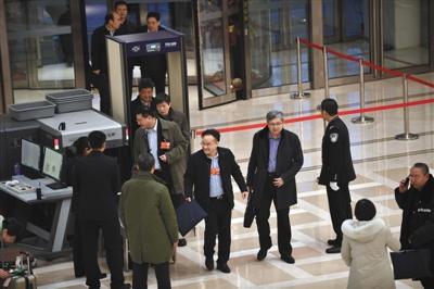 委员通过安检进入驻地大楼。