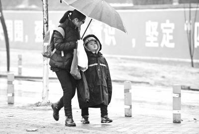 昨天早上,金银湖联通路旁,一位小学生穿着大人的棉衣走在上学的路上 记者李永刚 摄