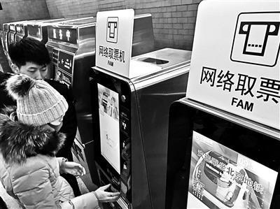 乘客在网络取票机上取地铁车票摄影/本报记者 黄亮