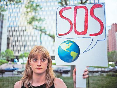 美国总统特朗普去年宣布美国退出应对全球气候变化的《巴黎协定》。图为在美国纽约,一名女子手持标语参加活动,抗议特朗普的决定。 新华社发