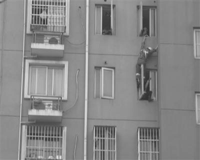 消防员从9楼滑下,将女子救下。