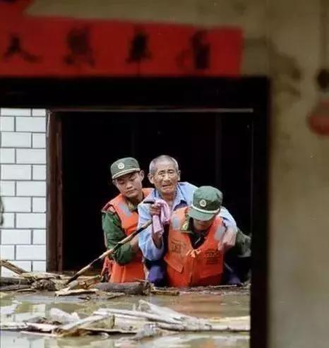 战士身背老人离开被淹的房子