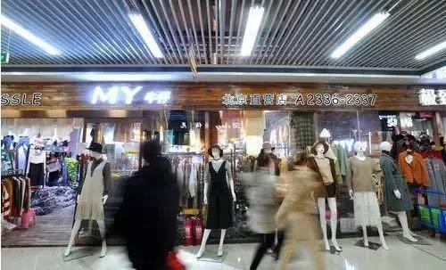 消费者从北京迁到沧州的明珠商贸城服装商户区店铺前走过