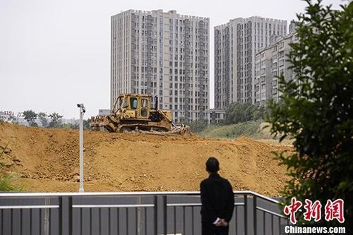 市民观望湖南长沙一楼盘工地上的推土机作业。 中新社记者 杨华峰 摄