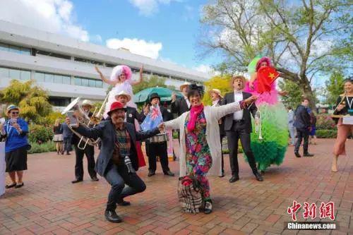 """资料图:2017年11月10日,全球闻名的""""墨尔本赛马节""""吸引不少中国游客。图为一对来自中国的夫妇伴着乐队的音乐和歌声,挥舞着中澳两国国旗翩翩起舞。中新社记者 陶社兰 摄"""