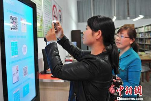 资料图:湖北省宜都市的市民在电子图书馆借阅终端上下载自己喜欢阅读的电子图书。曹礼达 摄