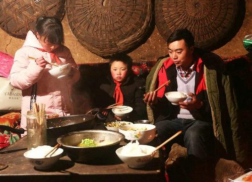 """前不久在网上走红的云南鲁甸的""""冰花男孩""""引起了中国网民对贫困问题的关注。图为""""冰花男孩""""(中)与家人一同吃饭。(美国《福布斯》双周刊网站)"""