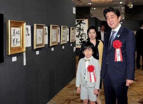 """△日本首相安倍晋三2013年8月7日展出了自己的书法作品""""以和为贵"""""""